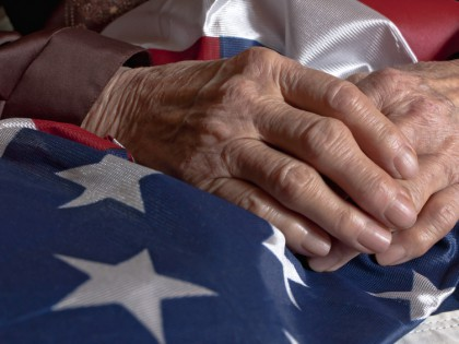 Old woman's hands holding an American flag