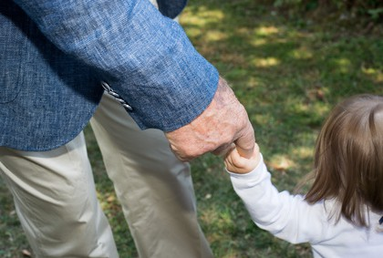 old retired man hand while holding newborn infant hand