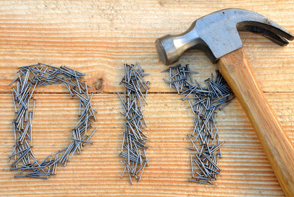 DIY (do it yourself) text from small nails and hammer on wooden desk background